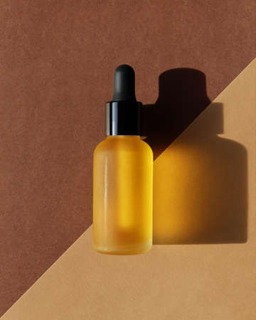 Vertical mockup of dropper oil bottle, double diagonal background. Banner, poster, central composition. Yellow cosmetic, serum, extract, emulsion, lotion. Brown terracotta colors. Hard light, flat lay 版權商用圖片