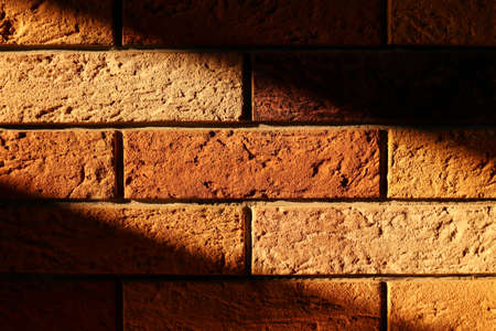 Decorative brick wall with diagonal strip of hard light and dark shadows. Texture stone. Horizontal template of background for banner with copy space. Monochrome brown with shades of yellow, red color