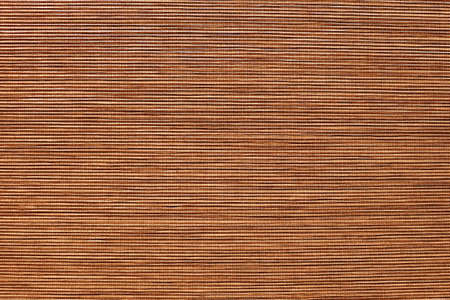 Bamboo mat closeup. Thin strips of wood sewn into fabric. Decorative textured backdrop. Horizontal template of background for banner with copy space. Monochrome brown with shades of beige, red color