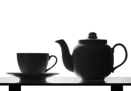 tea service: Teapot and cup on table. Silhouette Stock Photo