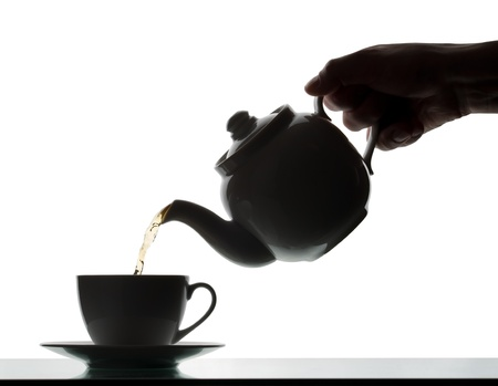 Teapot pouring tea into a cup. Silhouette photo