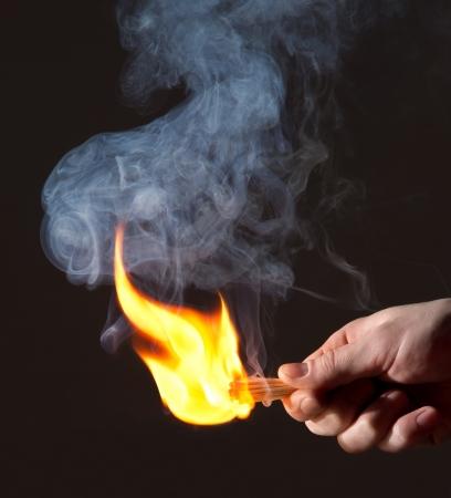 Burning match in hand. Smoke photo