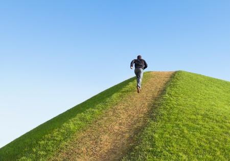 proposito: Camino a la colina contra el cielo. El hombre corrió hacia la parte superior. Símbolo de desarrollo o crecimiento profesional. Foto de archivo