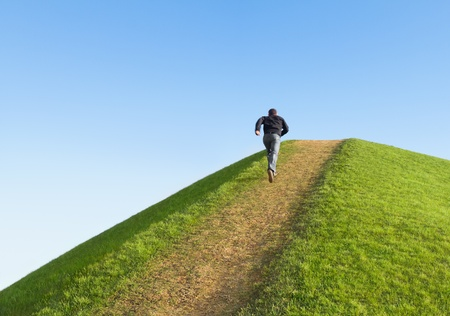 trail running: Pathway up the hill against the sky. Man ran to the top. Symbol development or career growth.