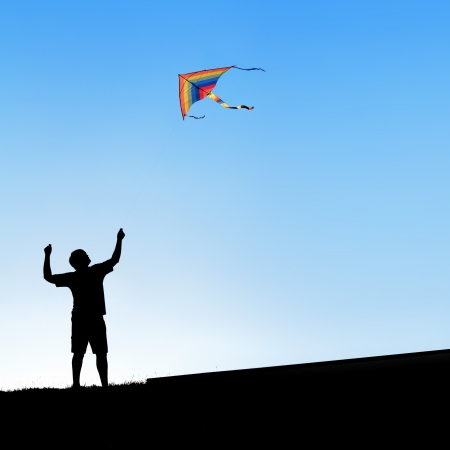 aloft: Kite in the sky. Silhouette of a man. Stock Photo