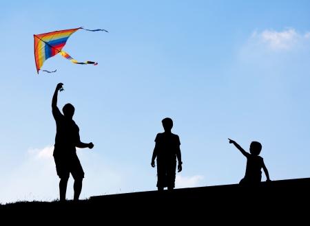papalote: Lanzamiento de un cometa en el cielo. Siluetas del hombre y sus dos hijos. Foto de archivo