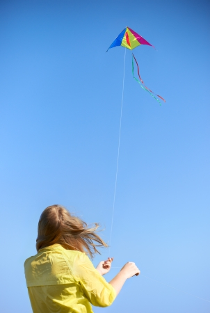 keeps: Kite on a rope against the sky  Girl keeps rope