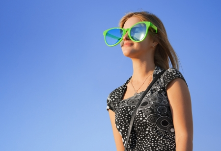 jesting: Symbol of summer vacation. Cheerful girl In large sunglasses