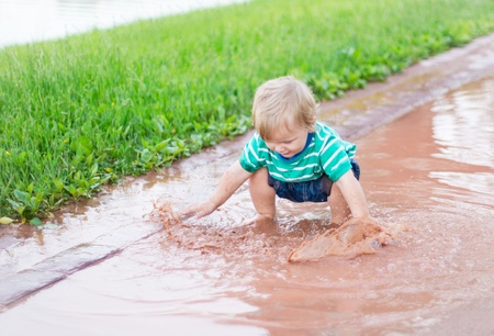 Child playing in a puddle after rain photo