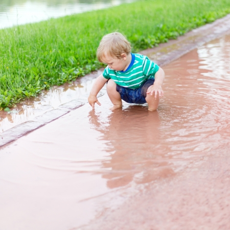 Child sits in a puddle and by means of a finger defines depth photo