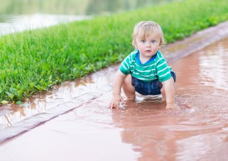 雨の後の水たまりで遊ぶ子供 写真素材