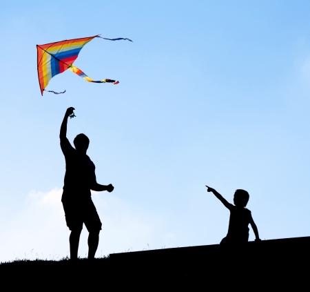 空のカイトを起動します。シルエットの男と子供たち。 写真素材
