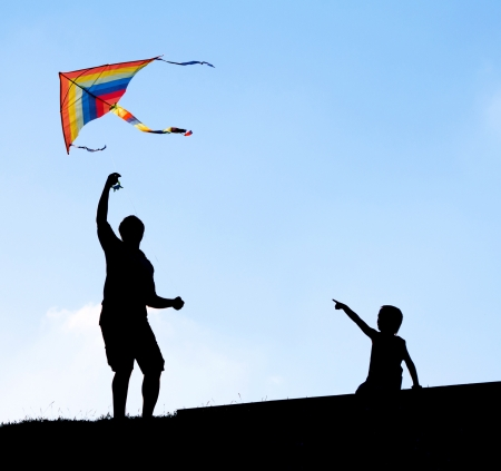 flying man: Launching a kite in the sky. Silhouettes man and children.