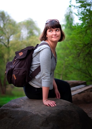 packsack: Female tourist sitting on a stone in the forest