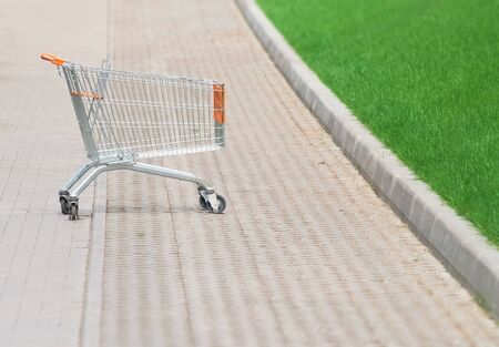 Shopping cart in the parking lot next to a supermarket photo