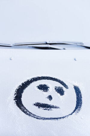 jesting: Smiley on the hood of the car. First snow Stock Photo