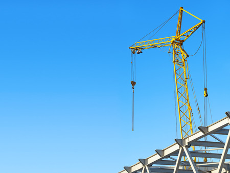 steelwork: hoisting crane against the blue sky with space for text