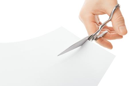 tijeras: Mano con las tijeras que cortan una hoja de papel blanco