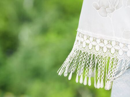 tranquilly: fragment of lace curtains on the background of green trees