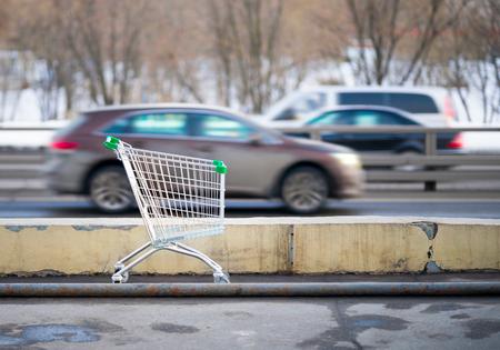 rushing: shopping cart on background rushing cars