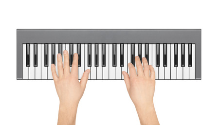 electronic piano: Hands playing electronic piano on a white background. View from the top.