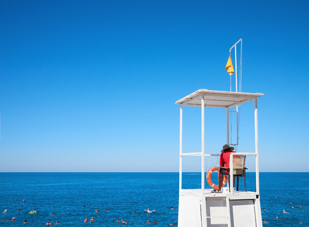 life guard stand: Lifeguard on tower to watching people floating in sea