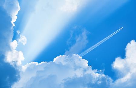 Vliegtuig dat in de blauwe lucht vliegt onder wolken en zonlicht
