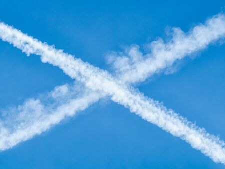 Traces of planes intersect in the blue sky