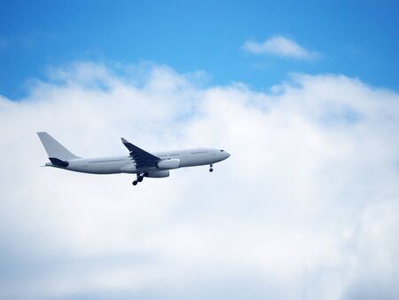 Passenger plane flies in the sky on the background of clouds