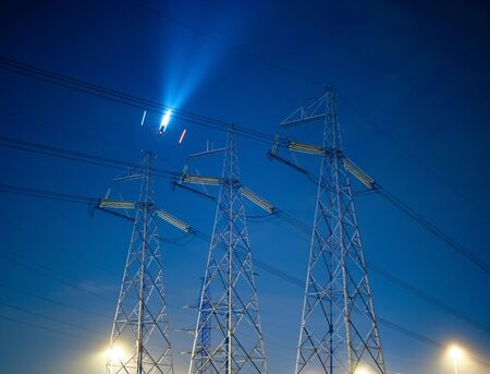 High voltage line against the night sky with a flying plane.