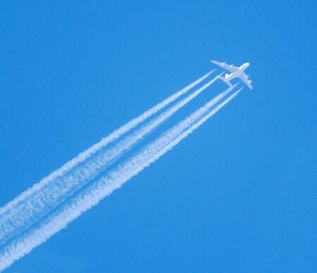 Passenger plane flying high in the blue sky Stok Fotoğraf