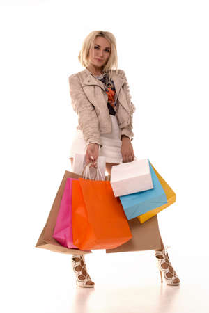 Beautiful blonde stands on a white background with purchases in her hands. The girl raised her leg and is glad that she bought so many things.