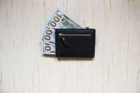 Wallet with money dollars lies on the table. Black wallet lies on a wooden table in the office with money.