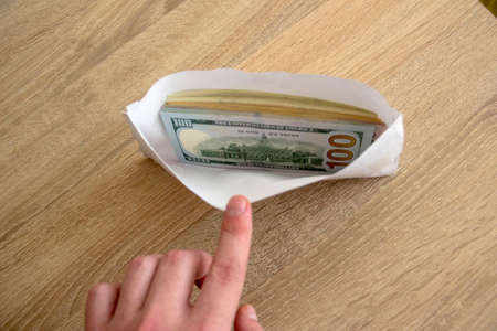 Man hand shows an envelope with money. Money dollars lie in a white envelope for an employee. The employee salary lies in an envelope.