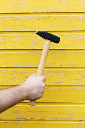 master: Hammer in a mans hand against a background of a yellow wooden wall