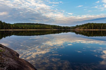 Landschap. Bosmeer bij zonsondergang en weerspiegeling van wolken in het water