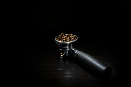 Coffee beans in a porta filter on a black background