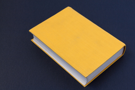 old closed book in yellow cover on a black background