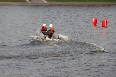 two teenagers are riding a sports inflatable motor boat. children's water motor sports Stock Photo
