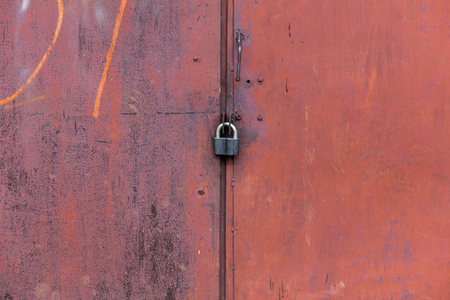 Rusty metal door closed on the padlock, old metal texture