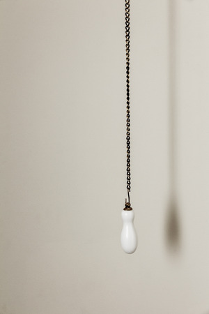 Hanging bronze chain with white ceramic handle for toilet flushing