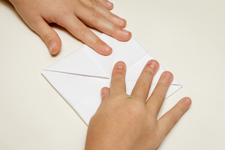 childrens hands and a piece of paper for origami