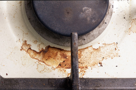 dirty modern gas stove with a cast-iron grill and stains of fat and burned food