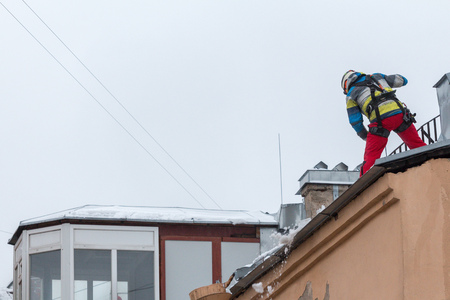 St. Petersburg, Russia - January 14, 2019: Industrial climber removes snow and frost from the roof of the house