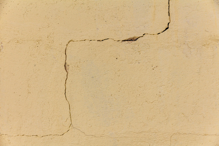 winding crack in a yellow plastered wall