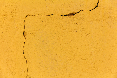 large winding crack in the yellow wall. abstract backdrop for design