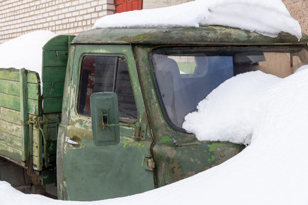 old car with a green wooden body and a metal cabin after a snowfall
