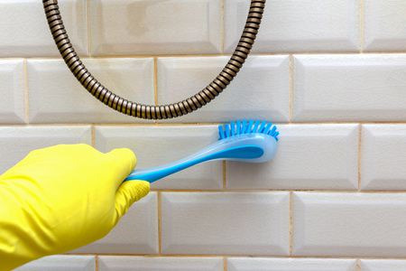 tile cleaning in the bathroom. brush in hand in yellow economic glove. Tile protection against mold and mildew