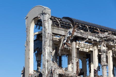 dilapidated reinforced concrete building. house demolition. dismantling the building in the form of an arch with a glass roof against the blue sky