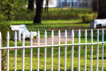 white iron fence in the park on a blurred background of benches and buildings Reklamní fotografie